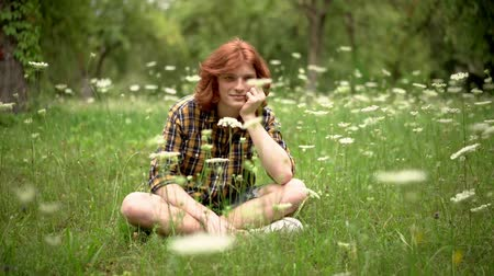redhair : Handsome Ginger Man Is Sitting With Crossed Legs On The Grass Surrounded By White Flowers. Young Guy With Red Hair In Checked Shirt Sits On The Grass Thinking. Slow Motion