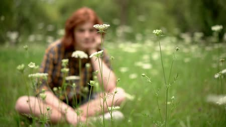 laboring : The Red-Haired Young Guy Sits on the Grass in the Garden. There are Wildflowers Around Him. His Hand Props Up His Chin. Casual Shirt Guy in a Cage. Slow Motion Footage. Close Up Shot. Stock Footage