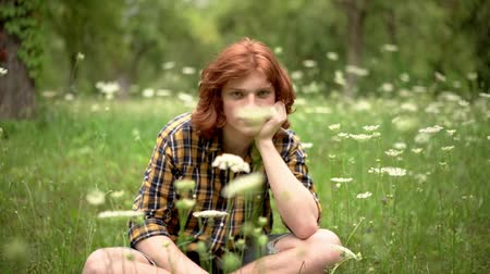 redhair : Charming Young Guy With Red Hair In Casual Cloth Is Sitting At The Grass In The Park. Pretty Ginger Guy Holds His Head And Sits On The Grass. Slow Motion
