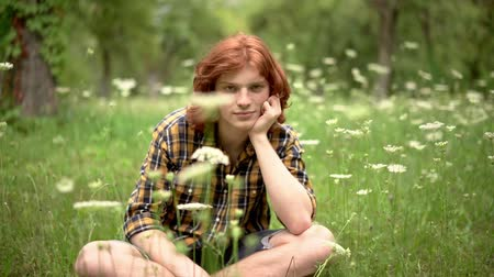 roodharige : A Young Redhead Guy is Sitting on the Lawn in the Garden. There are Wildflowers Around Him. His Hand Props Up His Chin. The Guy Looks Mysteriously in the Frame. Slow Motion Footage. Close Up Shot. Stockvideo