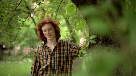 laboring : Red-Haired Young Guy Stands in a Garden Near a Tree. He Has a Romantic Look. The Wind Develops His Thick Red Hair. The Guy is Wearing a Plaid Casual Shirt. Slow Motion Footage. Close Up Shot.