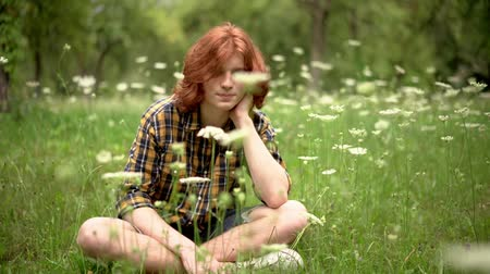 redhair : Smiling Young Boy With Red Hair Sits On The Grass Among White Flowers. Handsome Ginger Man With Crossed Legs Touches His Neck While Sitting On The Grass In The Park. Stock Footage