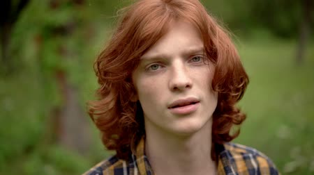 laboring : Young Guy with Red Hair Against the Background of a Green Garden. The Wind Develops His Thick Hair. The Guy Looks Puzzled. Slow Motion Footage. Close Up Shot.