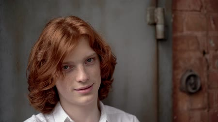 redhair : Young Guy with Thick Red Hair on a Background of Red Brick. The Guy Smiles a Little. On His Face Freckles. He is Wearing a White Shirt. Close Up Shot.