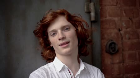 cheveux épais : Red-Haired Young Guy in a White Shirt Posing on the Street. The Wind Develops His Thick Red Hair. The Guy is Wearing a White Shirt. Slow Motion Footage. Close Up Shot. Vidéos Libres De Droits