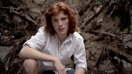redhair : Young Guy with Long Red Hair on the Street. He Squatted Down and Carefully Watched. The Guy Has a White Shirt and Denim Shorts. Slow Motion Footage. Close Up Shot.