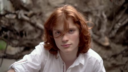 redhair : Pretty Red-Haired Boy In White Shirt Looks Pensively At Camera. Handsome Man With Red Hair Waving Around Captively Looks At Camera. Portrait. Slow Motion Stock Footage