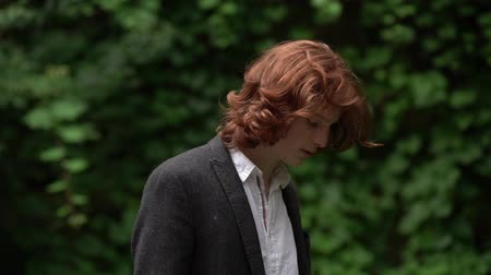femme rousse : Young Guy with Long Red Hair in the Garden. His Sight is Lowered. The Guy Has a Serious Look. He is Wearing a Black Jacket and a White Shirt. Slow Motion Footage. Close Up Shot. Vidéos Libres De Droits