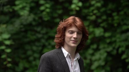 redhair : Cute Young Guy with Red Long Hair. He Smiles Gently. The Guy is Wearing a White Shirt and a Black Jacket. Behind the Guy are Green Trees. Slow Motion Footage. Close Up Shot.