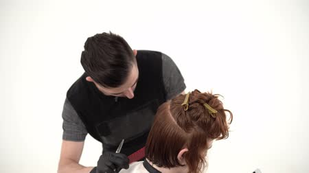pente : A Stylish Hairdresser and a Young Guy are in a White Studio. Master Cuts Red Hair Guy. In the Hands of the Guy Phone. He is Waiting For the Result. Close Up Shot.