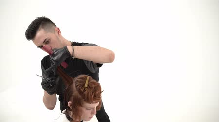limpar : Stylist Hairdresser Makes a Stylish Hairstyle Young Guy with Red Hair. The Guys Hair Will Be Shorter. They are in a White Room. Barber Man Looks Stylish.