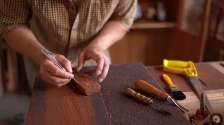 bevésett : Wood Carver At work In Workshop. Carving Piece Of Wood For Ship. Having Tools Nearby. Carving Art Concept.