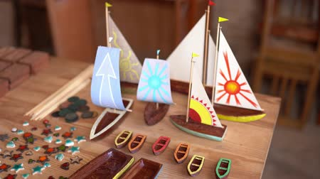 desenhada à mão : Small Wooden Ship Figures With Painted Canvas On Table In Workshop. Carving Art Concept.