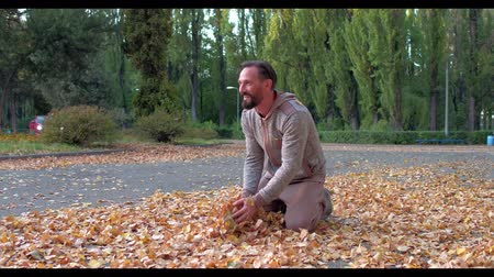 düşmüş : Sportive Man is Having Fun and is Doing Fitness on Nature. Middle-Aged Man with Dark Hair and Black Beard Doing Morning Excersises in Beautiful Autumn Park.