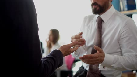 projeto : Two businessmen are communicating and discussing business ides by gestures. One businessman is wearing a white shirt and a black tie another a black suit.Businesswomen are working while sitting by the desk in the office on the background.