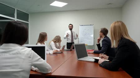 lecture : Businessman leader explaining a scheme on the whiteboard to young business team on the meeting with in office. He is wearing a white shirt, tie and black trousers. Four bosiness ladies a a young businessman are listening attentively while sitting by the t