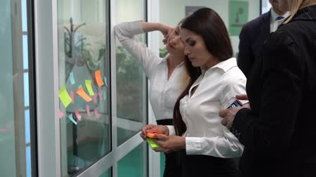 liste : Brunette businesswoman discrubing colorfull notes on the glass to colleagues. The business lady is holding orange stick notes. Colleagues are standing behind her. Stok Video