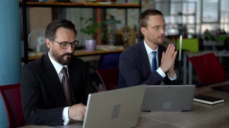 işbirliği yapmak : Business Partners are Working Together in Concentration. Stylish Men in Business Suit and Eyeglasses are Looking in Laptop. Blue Wall on Background Stok Video