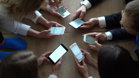 cooperar : Co-workers are working together. Group of people looking in their smartphones together on workplace. Modern Technology.