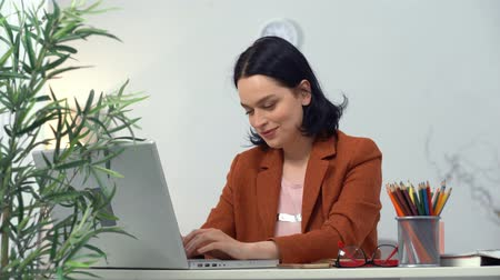 jó hangulatban : Confident Business Lady Sitting in Office. Good Mood Female Boss. Laptop and Flower in Pot on Forefront. Smart Woman Smiling