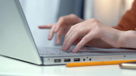 особенности : Close-Up Female Hands Tapping on Keyboard of Laptop in Office. Woman Working ar Workplace. Writing an Article.