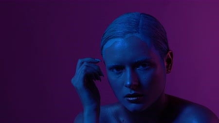 raises : Young Sexy Girl with Ponytail Hairstyle Moves Slowly In Neon Light in Studio. She Touches her Chin and Raises Head Up. Slow Motion Video. Stock Footage