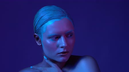 закрытыми глазами : High Fashion Skinny Model Studio Portrait in Neon Light. Girl with Beautiful Lightened Cheekbones and Blue Eyes. Deep Blue Background. Slow Motion Video Стоковые видеозаписи