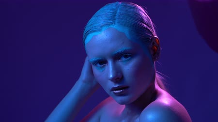закрытыми глазами : Sexy Skinny Blond Model Moves Slowly In Neon Light. She Looks Up and Turns in Profile. Violet Background. Slow Motion Fashion Video.