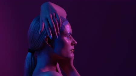 abriu : Attractive Female Blond Raises Hands Up to Head. Pink and Violet Studio Background. Left Side Profile Portreit.