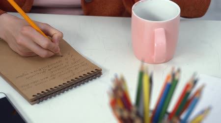 employed : Young Businesswoman Making Notes While Sitting At Table. Coffee Cup And Pencil Organizer On Table. Focus On Hand.