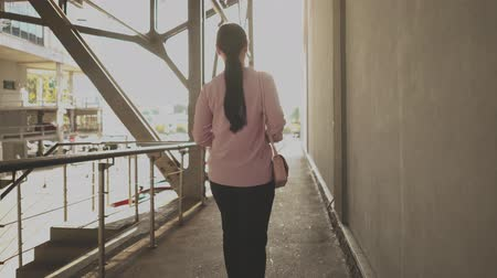 empregador : Buiness Female With Confident Stride Walking Down The Bridge Above Parking Lot. Going To Office. Business Concept.