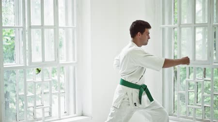 quimono : Handsome Man In White Kimono Doing Karate In Big Gym With High Windows. HAving Green Belt. Healthy Lifestyle Concept.
