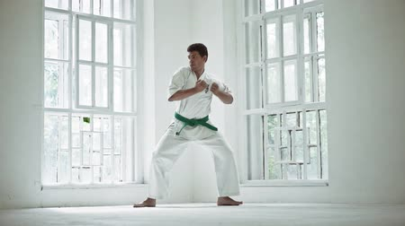 quimono : Tall Strong Male Standing In Karate Training Position In Big White Gym. Having Green Belt And Barefoot. Sport Concept. Vídeos