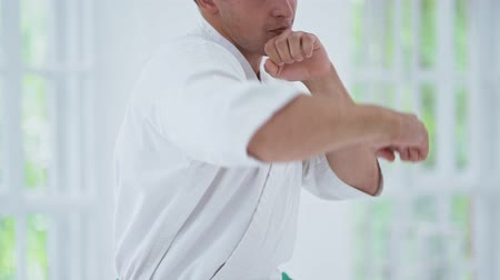 quimono : Training Of Defense Position In Karate. Man Wearing White Kimono And Stretching Fist. Karate Concept.