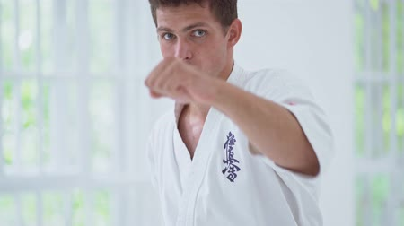 каратэ : Handsome Male In White Kimono Training Karate Combating In Gym.Looking Serious. Making Fists. Karate Concept. Стоковые видеозаписи