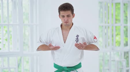 quimono : Skilled Karate Man Doing Breath Exercise While Training On White Window Background. Combat Concept. Vídeos