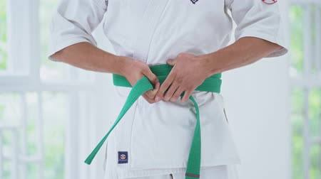 каратэ : Male Fastens Green Belt On White Kimono In Gym. Selective Focus On Hands Kimono And Belt. Karate Concept. Стоковые видеозаписи