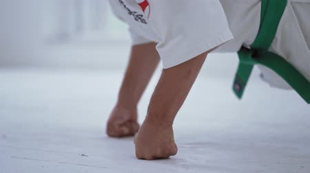 struggling : Martial Art Master In White Kimono Doing Push Ups In Gym. White Floor. Selective Focus On Strong Hands.