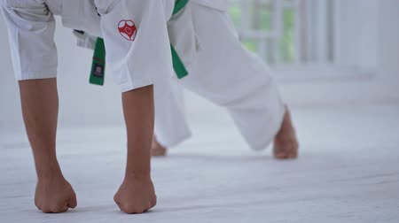 каратэ : Strong Man In White Kimono Doing Push Ups On Fists. White Floor. Martial art Concept. Sport Attitude.