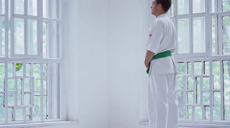 каратэ : Tall Karate Trainer In Snow White Kimono Standing In White Big Gym. Looking Through Window, Concentrated. Стоковые видеозаписи