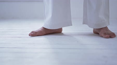 quimono : Tall Karate Master Standing Middle Gym In White Kimono. Selective Focus On Feet In Karate Uniform.