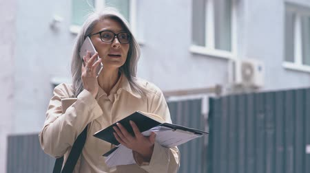 same : The Middle-aged Asian Woman Is Standing In The Street With Opened Notebook And Many Documents In Her Hand. She Is Speaking On The Telephone At The Same Time .The Business Lady Looks Busy Stock Footage