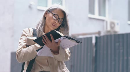listens : The Middle-aged Asian Woman Is Standing In The Busy Street .She Is Speaking On The Telephone and Writing Information In Her Notebook At The Same Time.The Businesswoman Is Also Holding Documents In Her Hand Stock Footage