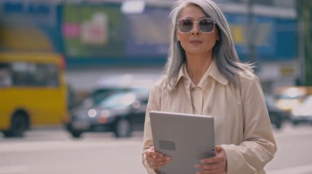 looking for : Middle-aged Business Woman Is Standing In The City Center And Using Her Tablet.She Is Wearing Stylish Sunglasses.The Cars Are Passing By Her.Sometimes The Lady Looks Aside Stock Footage