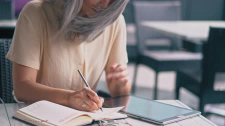 explodindo : Middle-Aged Good-Looking Asian Woman In A Trendy Shirt Is Sitting At The Table In The Cosy Cafe.The Businesslady Is Writing Information In Her Notebook,The Wind Is Blowing Her Hair.Close up Shooting Stock Footage