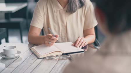 escritórios : The Middle-Aged Asian Woman Is Sitting At The Office And Speaking With A Woman Sitting With Her Back.The First Woman Has got A Pen In Her hand, Notebook And A cup Of Coffee Is Near Her.