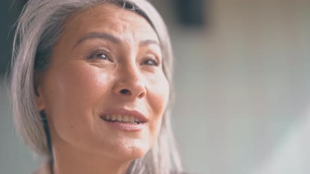 söylemek : The Middle-aged Asian Woman With A grey hair Is Speaking And Smiling.Close up Shot Stok Video