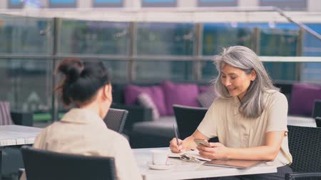 management manager : The Middle-Aged Asian Woman Is Sitting At The Office And Speaking With A Woman Sitting With Her Back.The First Woman Has got A Pen In Her hand, Notebook And A cup Of Coffee Is Near Her.She Is Making Notes Stock Footage