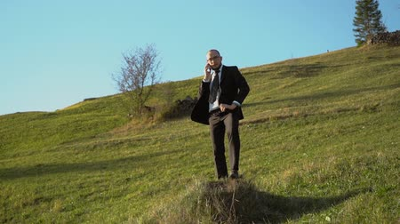 A Man In A Black Suit Speaks On A Cell Phone Standing The Mountain. Hill With Grass And Blue Sky On The Background. Slow Motion Business Concept