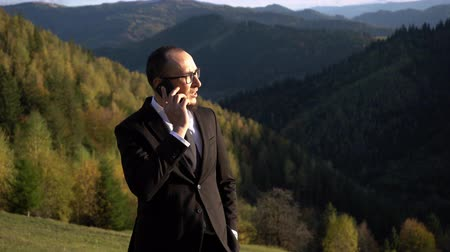 Young Office Worker Is Talking On The Phone In The Mountains And Looking To The Right. He Is Serious And Focused. The Camera Slowly Zooms In. Business Concept Video Vídeos